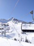 Ski lift carries skiers Stock Photos