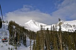 Ski Lift Carries Skiers zur Bergspitze stockfoto
