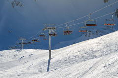 Ski lift carrying skiers, snowboarders on a bright sunny winter day Stock Photos