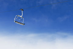 Ski lift chair on bright blue sky Royalty Free Stock Photos