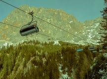 Ski lift chairs above trees Stock Photo