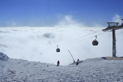 Ski lift. Climb up above the clouds clear day Royalty Free Stock Image