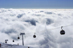 Ski lift. Climb up above the clouds clear day Royalty Free Stock Photography