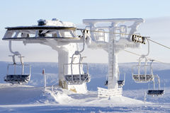 Ski lift covered in snow. Empty ski lift covered in snow in bright sunshine stock photography