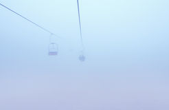 Mountain ski-lift in fog Stock Images