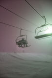 Ski lift in the fog. Two snowboarders ride a ski lift in the fog Stock Photos