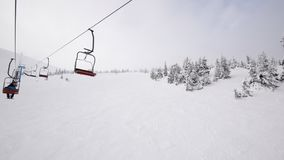 On a ski lift in foggy mountains stock video