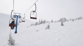 On a ski lift in foggy mountains stock video footage