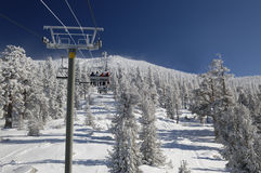 Ski lift at Lake Tahoe Skiing Resort. Skiers are riding lift on a very cold day at one of the Lake Tahoe ski resorts (Sierra Nevada, USA Royalty Free Stock Photography