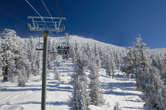 Ski lift at Lake Tahoe Skiing Resort. Skiers are riding lift on a very cold day at one of the Lake Tahoe ski resorts (Sierra Nevada, USA Royalty Free Stock Photo