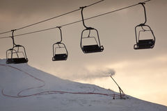Ski lift line and working artificial snow gun Royalty Free Stock Images