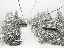 Ski lift in mist. Empty ski lift in mist between snow covered trees Stock Image