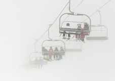 Ski lift in the mist. Skiers sitting and riding with ski lift up the foggy mountain Royalty Free Stock Image