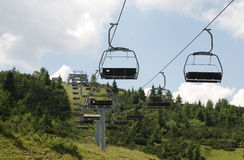 Ski Lift on Monte Zoncolan in Summer. An empty chair ski lift on Mount Zoncolan in Friuli, Italy - out-of-use during the summer Stock Image