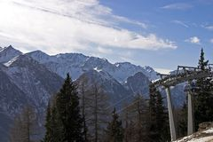 Ski lift in mountains. Scenic view of ski lift with snow capped Dolomite mountains and cloudscape background Royalty Free Stock Photos