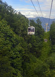 Ski lift in the mountains carrying passengers to hiking trail Stock Photos