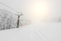 Ski lift over snow mountain in ski resort . Royalty Free Stock Photo