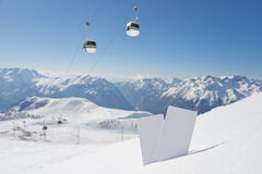 Ski lift pass and panorama. Lift pass card in snow with blurred ski-lift and mountain range. Concept to illustrate Wintersport admission fee Royalty Free Stock Images