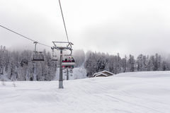 Ski lift with passengers in the chair. Traversing a snow covered mountain slope as it starts the ascent over the evergreen pine plantations to the distant stock image
