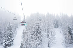 Ski lift with passengers in the gondola. Passing over a clearing through a snow covered plantation of evergreen conifers in a beautiful winter landscape stock images