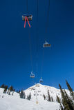 Ski Lift riding Up Mountain. In Fernie Alpine Resort on a blue sky day royalty free stock images