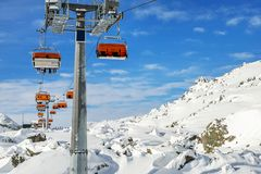 Ski lift ropeway on hilghland alpine mountain winter resort on bright sunny day. Ski chairlift cable way with people enjoy skiing