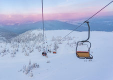 Ski lift with seats going over the mountain and paths from skies. And snowboards Royalty Free Stock Image