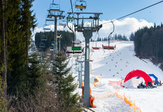 Ski lift with seats going over the mountain. And paths for skies and snowboards in a ski-resort in winter period Royalty Free Stock Photography