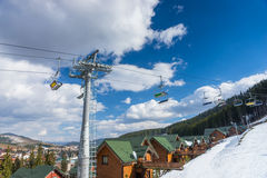 Ski lift with seats going over the mountain and wooden cottages. In a snow-covered ski-resort Stock Photo