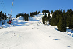 Ski lift and skiing tracks on snow Alps mountains Stock Image