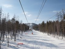 Ski lift on the slope of a forested Royalty Free Stock Images