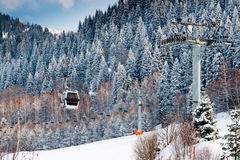 Ski lift and snow covered mountains with pine trees background at resort Ak Bulak, Kazakhstan Royalty Free Stock Images