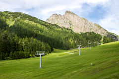 Ski lift in summer. Green mountain valley in summer with ski lift Stock Photo