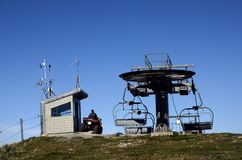 Ski lift in summer and man on quad. In charge of maintenance, Semnoz, Savoy, France Royalty Free Stock Image