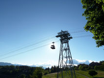 Ski lift in summer and mountain landscape. Alpine ski lift blocking the sun, in a mountain  landscape with trees Royalty Free Stock Photos