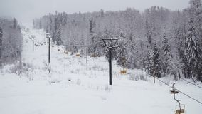 Ski lift under snowfall. Ski lift in the mountains under snowfall stock video