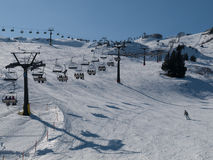 Ski lift. Winter downhill skiing resort in Alps Stock Image