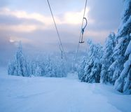 Ski lift in winter snowy landscape in mountains of spruce forest Stock Images