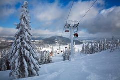 Ski lift in winter snowy landscape in mountains of spruce forest Stock Image