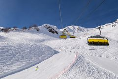 Ski liftYellow chair lifts against the beautiful mountains. royalty free stock images