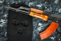 Ski mask and ak 47 on a camouflage background Royalty Free Stock Photography