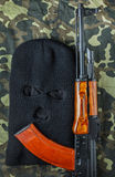 Ski mask and ak 47 on a camouflage background Stock Photography