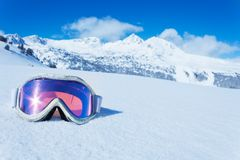 Ski mask. Ski and snowboard mask in the snow with copy space and mountain on background