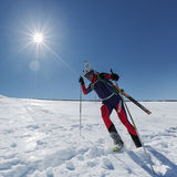 Ski mountaineer runs down the mountainside with skis strapped to backpack Royalty Free Stock Photos