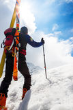 Ski mountaineer walking up along a steep snowy ridge with the s Stock Photo