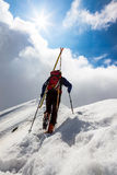 Ski mountaineer walking up along a steep snowy ridge with the s. Kis in the backpack. In background a dramatic sky with a shiny bright sun. Concepts: adventure royalty free stock photos