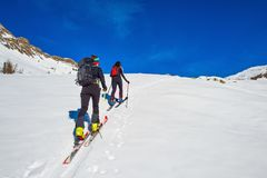 Ski mountaineering two girl uphill towards a mountain.  Royalty Free Stock Photo