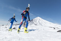 Ski mountaineering: two ski mountaineer climb to mountain with skis strapped to backpack Stock Image
