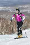 Ski mountaineering, Vertical race: smiling girl ski mountaineer climb on skis on mountain. MOUNTAIN MOROZNAYA, ELIZOVO, KAMCHATKA, RUSSIA - APRIL 25, 2014 Royalty Free Stock Photos