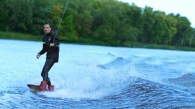 Ski nautique de Wakeboarder sur la rivière derrière le bateau Cavalier d'embarquement de sillage banque de vidéos